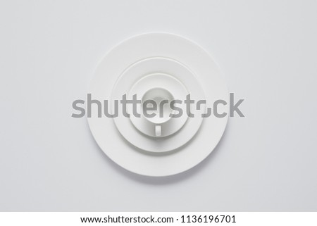 top view of arranged stack of different plates and cup on white table, minimalistic concept #1136196701