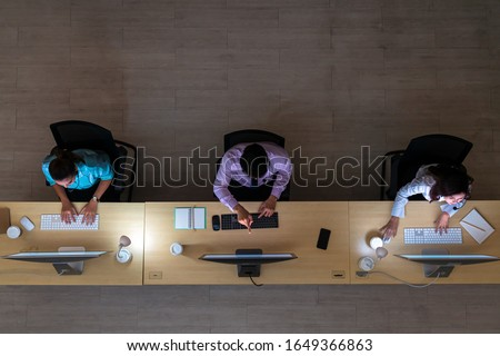 Top view of Asian Male customer care service working hard late in night shift at office,call center department,worker and overtime,team work with colleagues for success