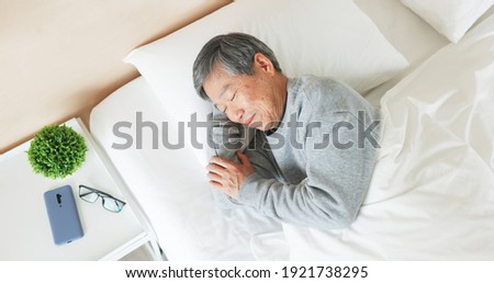 top view of asian senior man lying on bed sleep well with smile in bedroom at home
