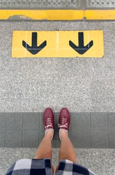 Top view of Asian woman standing on platform waiting for sky train with sign or symbols of two black-yellow back arrows, Bangkok, Thailand.