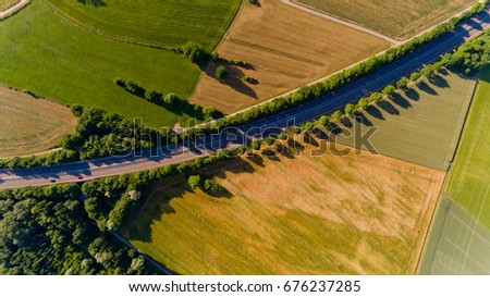 Top view of asphalt road passes through the field.