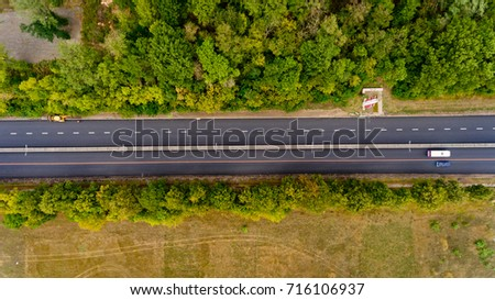 Top view of asphalt road passes through the field and forest. #716106937