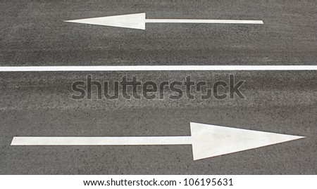Top view of asphalt with two directional arrows and a line between them