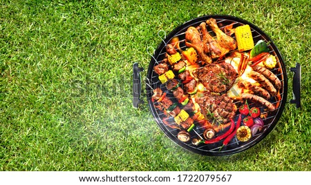 Top view of assorted delicious grilled meat with vegetables on barbecue grill with smoke and flames in green grass