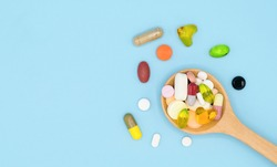 Top view of assorted pharmaceutical medicine pills, tablets and capsules in wooden spoon isolated on blue background, Dietary supplement healthcare product, Copy space.