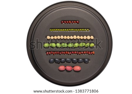 Top view of assortment of dry black,red,green,soy beans and shelled peanut in lines in metal plate isolated on white background.Different dry legumes for eating healthy