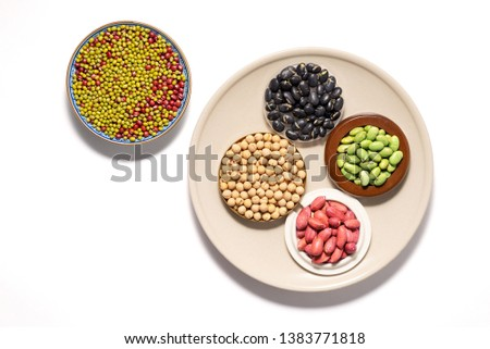 Top view of assortment of dry black,red,green,soy beans and shelled peanut in plate and bowl over white background.Different dry legumes for eating healthy