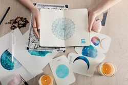 Top view of astrologer holding notebook with watercolor drawings and zodiac signs on cards on table