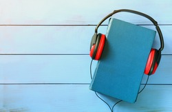 top view of audio book concept, blue book cover and headphones over wooden table