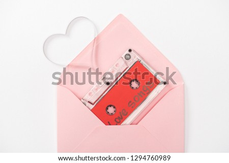 top view of audio cassette with 'love songs' lettering and heart symbol in envelope isolated on white, st valentines day concept