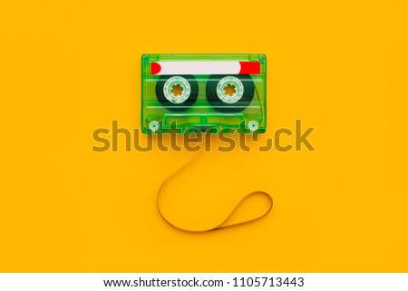Top view of audio cassette with tangled tape on bright yellow background with copy space, minimalistic composition #1105713443