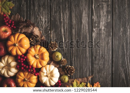 Top view of  Autumn maple leaves with Pumpkin and red berries on old wooden background. Thanksgiving day concept. #1229028544