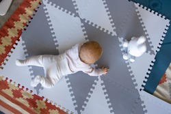 Top view of baby crawling on mat to hare toy. Infant child in home interior. Childhood concept
