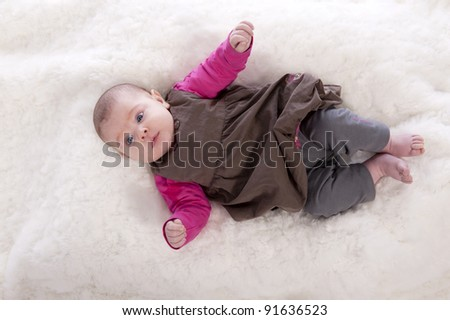 top view of baby girl lying on a beige carpet