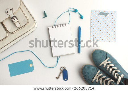 Top view of bag content accessories collection in blue color theme with bag, shoes, pen, blank notepad, paper tag,headphone and keys