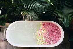 Top view of bath tub filling with water with flowers and lemon slices. Organic spa relaxation in luxury Bali outdoor bathroom.