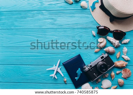 Top view of beach summer accessories with copy space. Lay flat holiday fashion background on blue wooden table or floor.Travel concept.