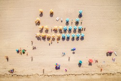 Top view of beach with colourful umbrellas and people bathing in the sun in South Beach Miami, Florida, USA.