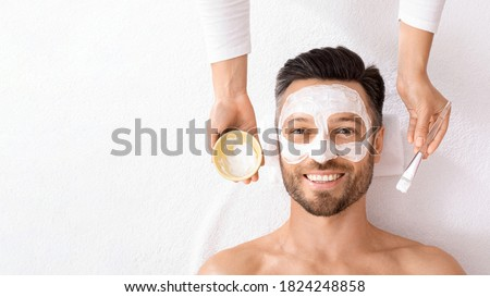 Top view of bearded cheerful man getting face treatment at modern spa salon. Female attendant applying white face mask on middle aged man face. Male face care concept, panorama with free space