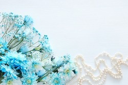 Top view of beautiful and delicate blue flowers arrangement next to pearls necklace on white wooden background. Copy space