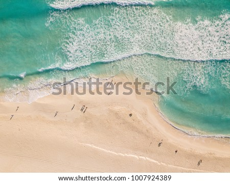Top view of beautiful beach. Aerial drone shot of turquoise sea water at the beach - space for text. Caribbean seaside beach with turquoise water and big waves aerial view. Cancun beach aerial view.