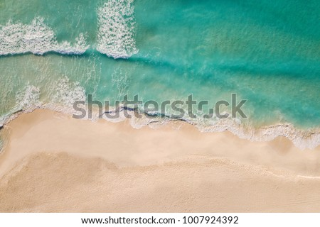 Stock Photo Top view of beautiful beach. Aerial drone shot of turquoise sea water at the beach - space for text. Caribbean seaside beach with turquoise water and big waves aerial view. Cancun beach aerial view.