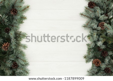 top view of beautiful evergreen fir twigs with pine cones on white wooden background     #1187899009
