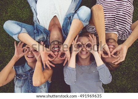 Top view of beautiful stylish friends making glasses of fingers, looking at camera and smiling while lying on grass