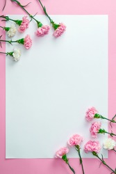 Top view of beautiful tender carnation flowers and blank card on pink background