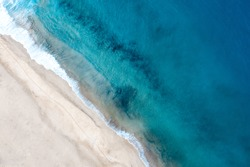 Top view of beautiful white sand beach with turquoise ocean water, aerial drone shot