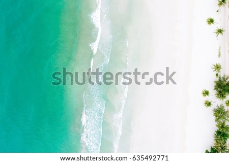 Top view of beautiful white sand beach with turquoise sea water and palm trees, aerial drone shot