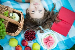 top view of beautiful woman with picnic basket, fruits and book in summer park