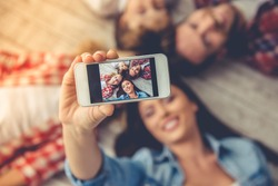 Top view of beautiful young parents and their children doing selfie using a smart phone and smiling while lying together on the floor at home