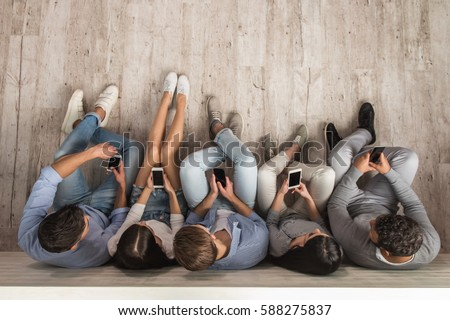 Top view of beautiful young people in casual clothes using smartphones while sitting together on the floor #588275837