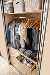 Top view of beautifully folded boxes and things of a blue hue hang on the shoulders in the wardrobe. Concept of perfect organization and accuracy in the house