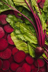 Top view of beet slices, beet leaves and one beet and beetroot for food background with copy space.