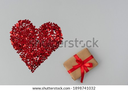 top view of big red heart made from little glittering confeti of heart shapes, gift box with red ribbon is near, protective measures on valentines day, new reality. Copy space Stok fotoğraf ©