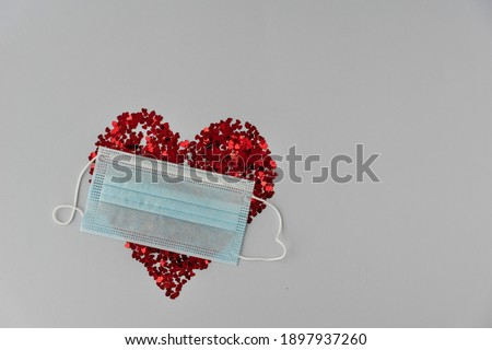 top view of big red heart made from little glittering confeti partly covered with medical mask, protective measures on valentines day, new reality. Copy space Stok fotoğraf ©
