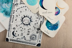 Top view of birth chart and cards with zodiac signs on wooden table