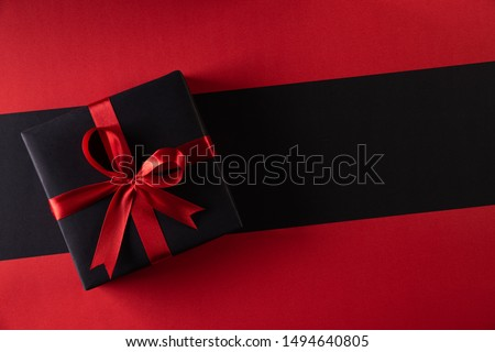 Top view of black christmas boxes with red ribbon on black background with copy space for text. black Friday and Boxing Day composition.