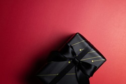 Top view of black christmas gift box with red and black ribbons isolated on red background. Shopping concept christmas day, valentine's day and black Friday sale composition.