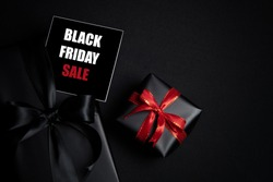 Top view of Black Friday Sale text with black gift box isolated on black background. Shopping concept boxing day and black Friday composition.