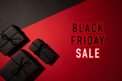 Top view of black gift box on black and red background with copy space for text. black Friday and Boxing Day composition.