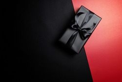 Top view of black gift box with black ribbons isolated on red and black background. Shopping concept boxing day and black Friday sale composition.