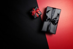 Top view of black gift box with red and black ribbons isolated on red and black background. Shopping concept boxing day and black Friday sale composition.