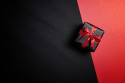 Top view of black gift box with red ribbon isolated on red and black background. Shopping concept boxing day and black Friday sale composition.