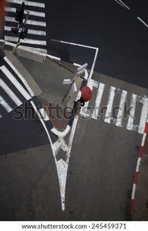 Top view of black & White cross road: Traffic island, pedestrian crossings and traffic lights on a rainy day. A Pedestrian with a red umbrella cross the street.