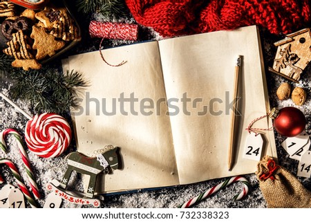 Top view of blank book arranged with Christmas decor and sweets in studio.  #732338323