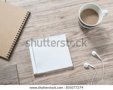 Top view of blank compact disc (CD) with cover , earphones, notebook and coffee on wooden background