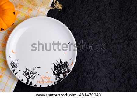 Top view of blank halloween plate on black background, with blank space and decorated.